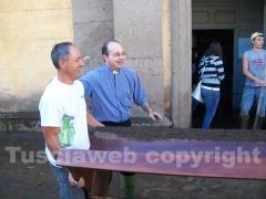 Don Mario Zanasi a lavoro per spalare il fango
