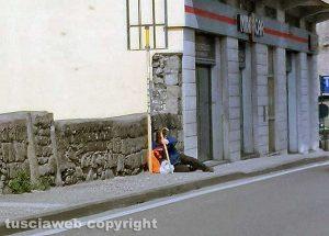 Viterbo - Anziano seduto a terra mentre aspetta l'autobus