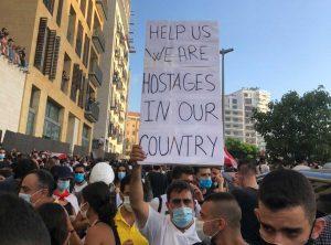 """Beirut, proteste anti governative - Nel cartello in inglese: """"Aiutateci, siamo ostaggi nella nostra nazione"""""""